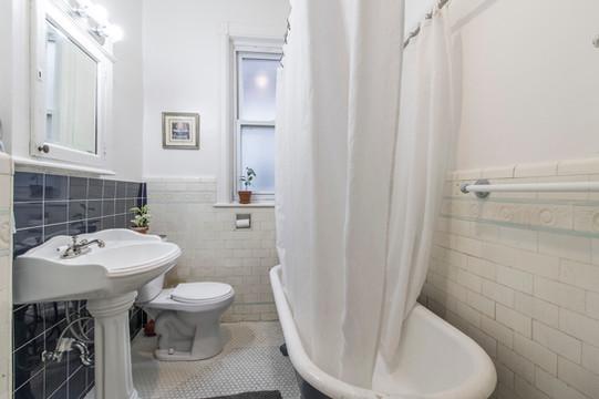 51st Street Twin - Hall bath with original wet bed tile floor