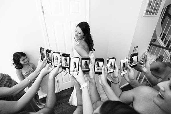 bridal party using cell phone to photograph bride