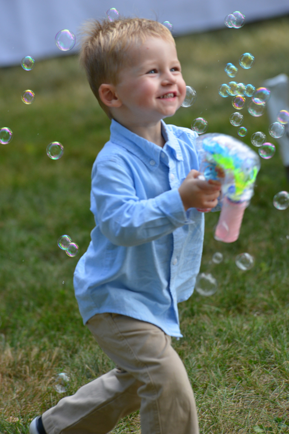 A young boy enjoys playing with a bubble maker at a wedding reception