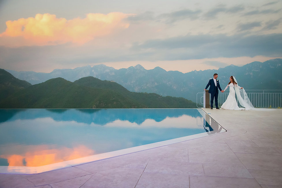 Bride and groom next to infinity pool