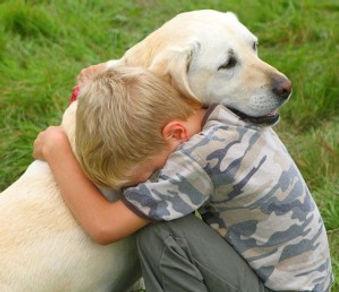 boy hugging golden dog