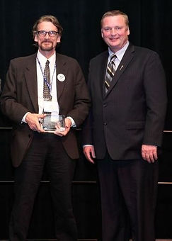 John Williams, Inventor and CEO of Roundspring Technologies, Inc. accepts the 2014 Minister's Award of Excellence in Safety Innovation from the Alberta's Minister of Transportation,  The Honorable Wayne Drysdale March 24, 2014