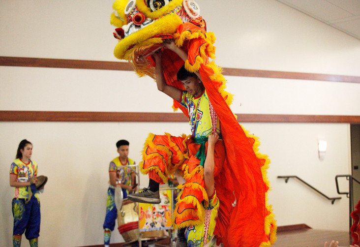 A youth participant carrying a brightly adorned dragon costume is lifted in the air while performing a Chinese ceremonial lion dance. The Buu Kim Tu Dragon and Lion Dance Association performs cultural dances throughout the Bay Area, this year, featured at World Refugee Day in the Campbell Community Center on June 14.