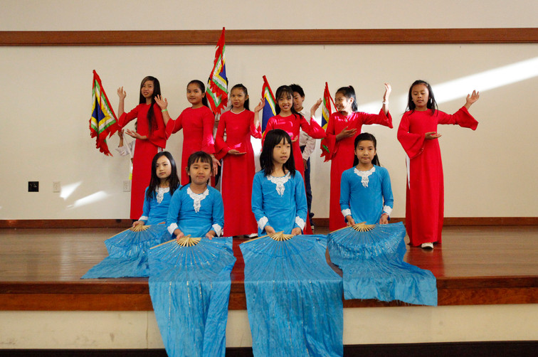 Community youth dressed in vibrant ethnic clothing begin a Vietnamese cultural dance at World Refugee Day in Campbell, Santa Clara on June 14.
