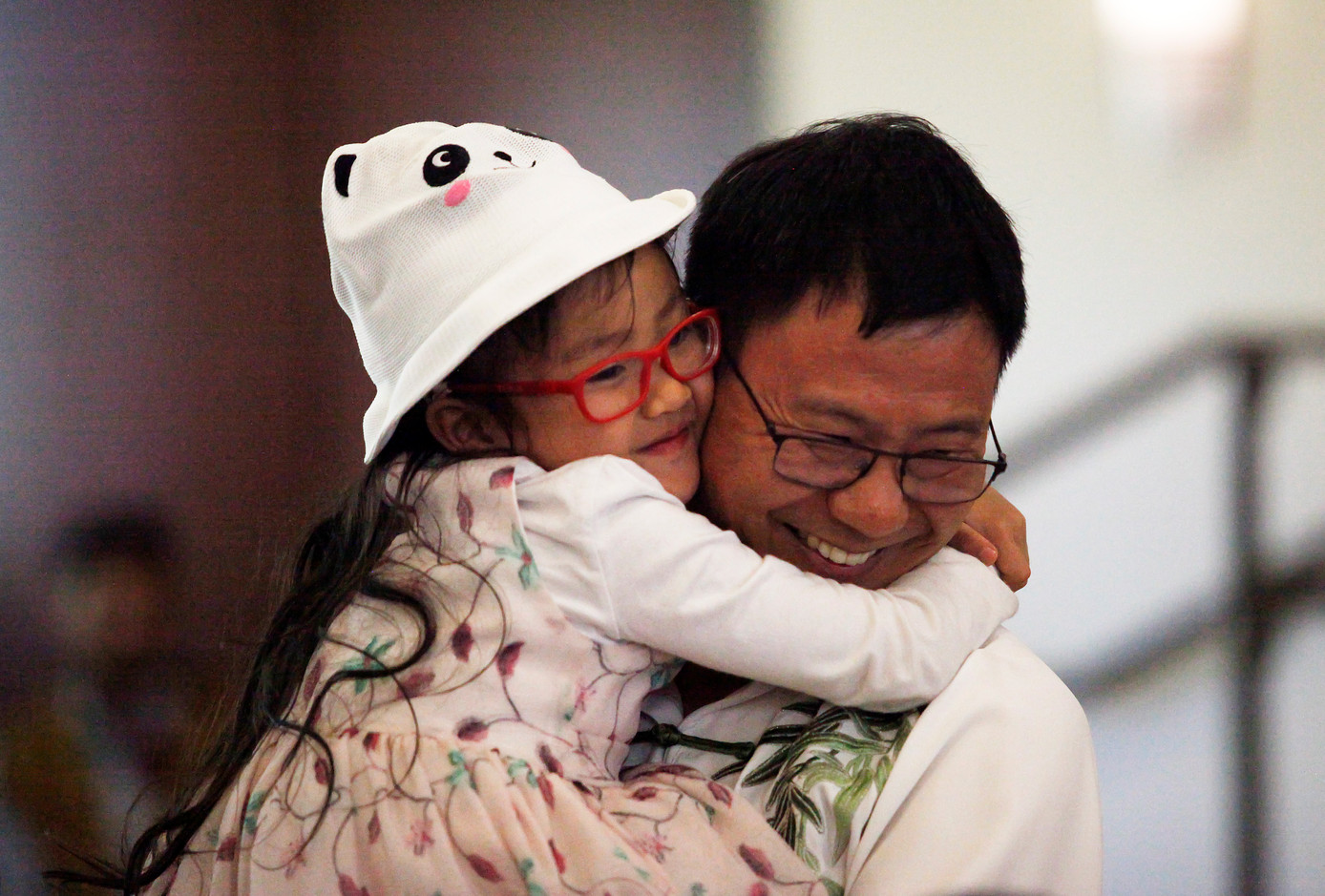 Esther Tang embraces her father, Zhong Liang Tang, after his performance of the Chinese martial art tai chi at World Refugee Day in Campbell, Santa Clara, on June 14.