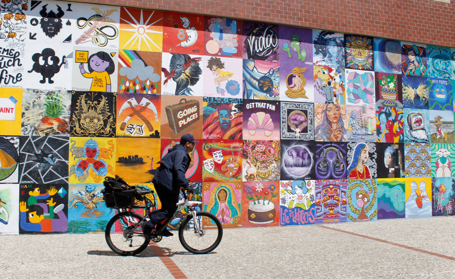 """A cyclist rides by the """"100 Block Mural Project"""" painted on a wall of the Valley Title building on First Street. (Camille Gandotra/Mosaic)"""