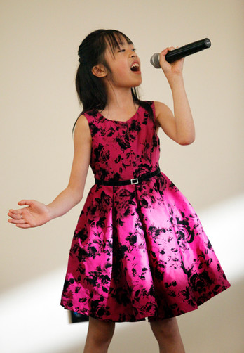 """Youth participant from the Vietnamese cultural group, sings """"This Girl is on Fire"""" by Alicia Keys at World Refugee Day in Campbell, Santa Clara, on June 14."""