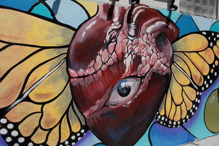 """A detail from a mural on Fountain Alley titled """"Heartsong"""" by artist Francisco Ramirez depicts an eye in the center of a heart with monarch wings. (Jocelyn Cervantes/Mosaic)"""