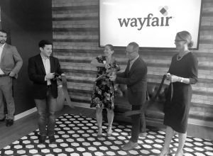 FROM LEFT, Wayfair's Site Director Alan Marblestone, VP of Sales Liz Graham and CFO Michael Fleischer, and Quincy Hentzel, CEO of the Portland Regional Chamber of Commerce, take part in a ribbon cutting ceremony for Wayfair's expanded facility at Brunswick landing. CHRIS QUATTRUCCI / THE TIMES RECORD