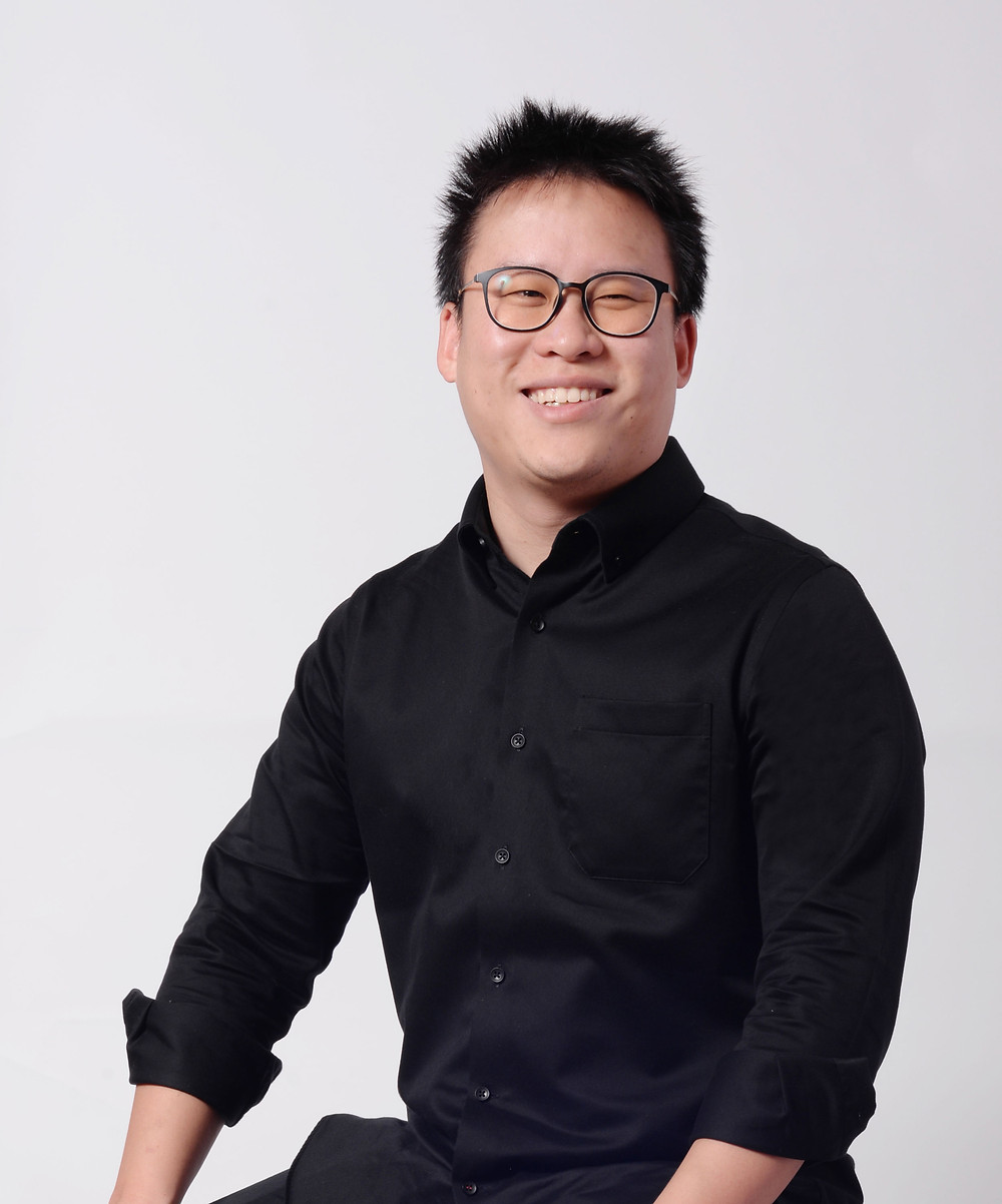 CEO of Supara Group WIn Thanapisitikul sits in a chair smiling looking at the camera in a black GQ Essentials button-down long-sleeve dress shirt.
