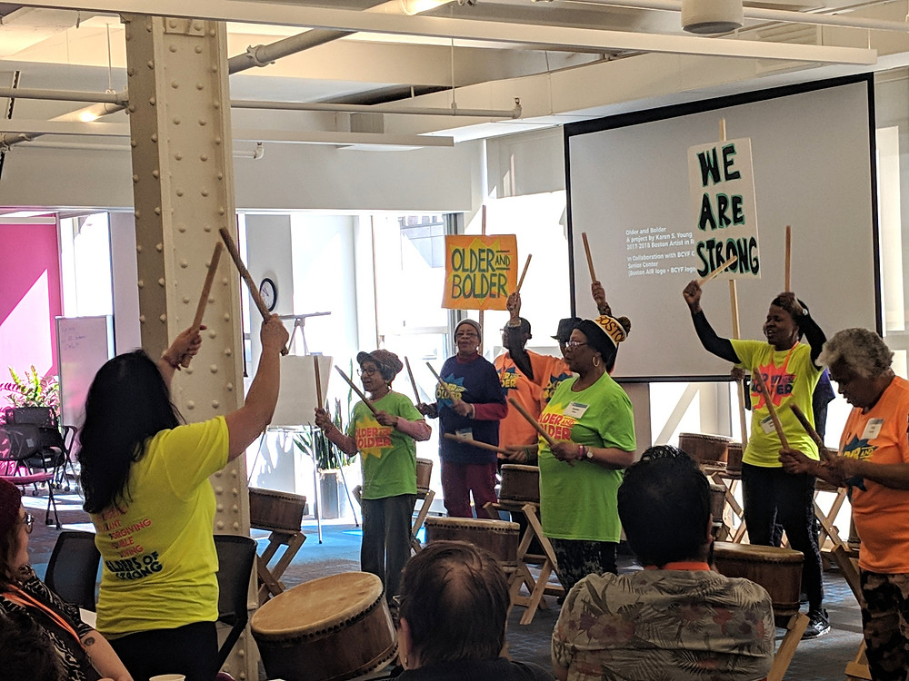 """People wearing bright green and yellow shirts playing taiko drums and holding signs that say """"Older and Bolder."""""""