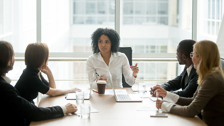 black woman at head of desk with diverse