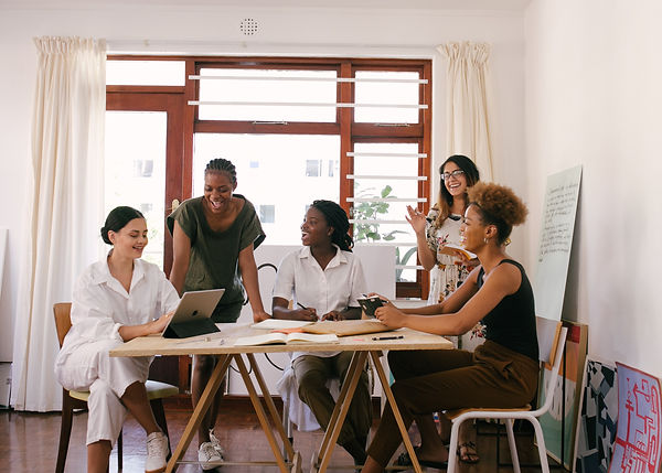 women of color in a meeting around table