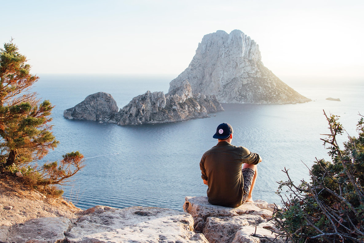rear-view-of-man-sitting-on-rock-by-sea-