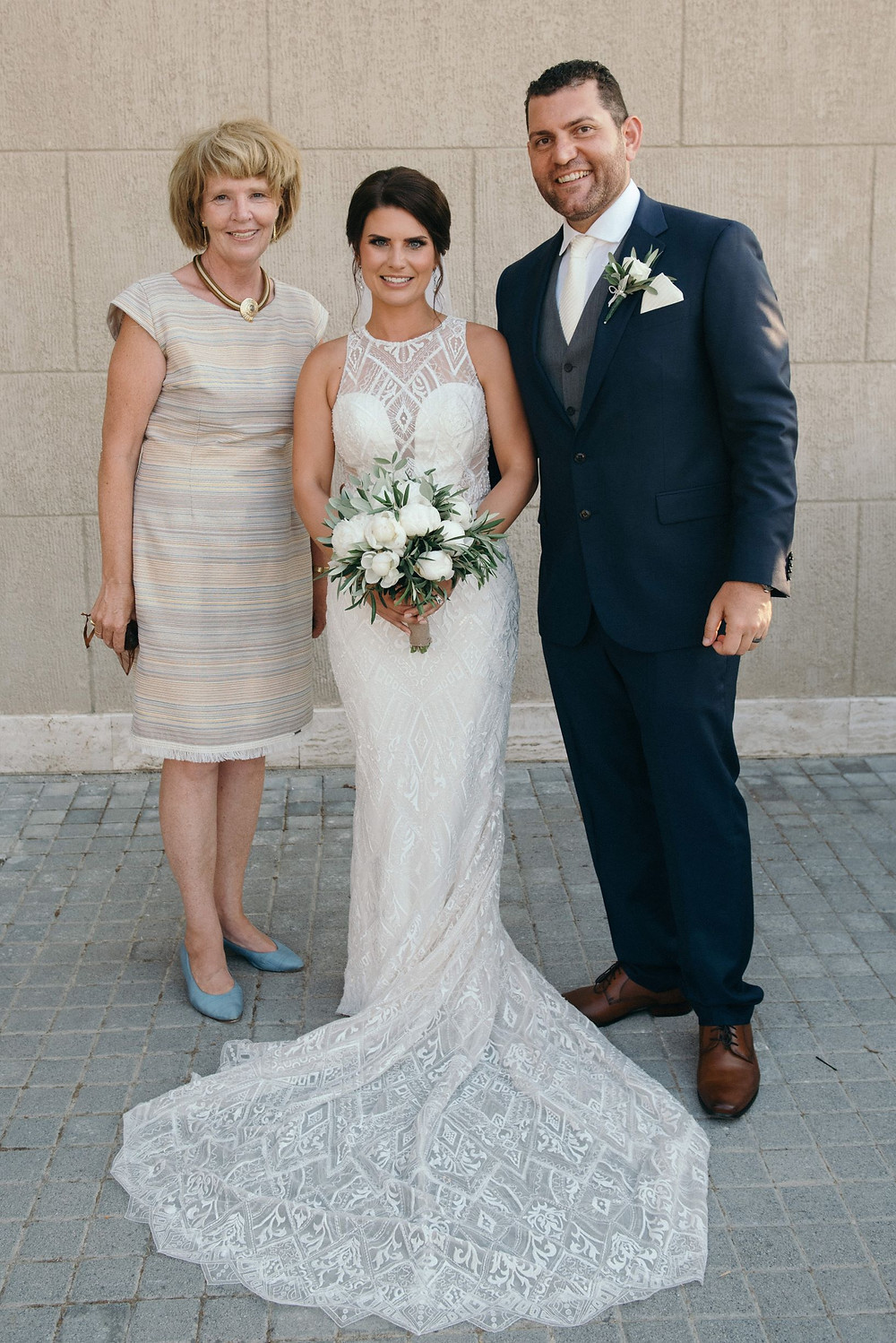A couple on their wedding day, standing beside Sarah Hatjipavlis, their wedding celebrant and founder of Grecian Ceremonies