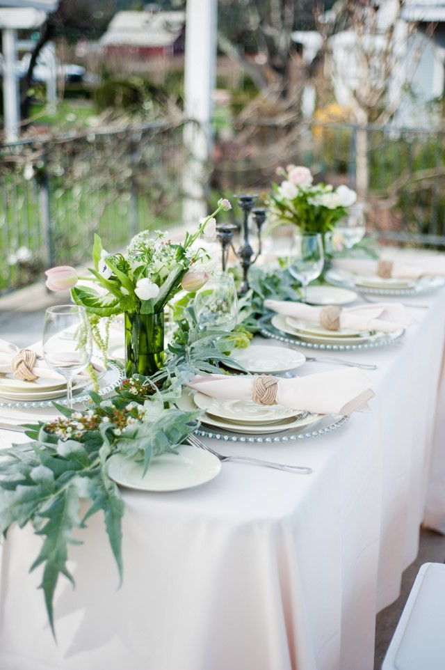 Artichoke leaves table runner with off-white table cloth and white flowers in votives on a reception table