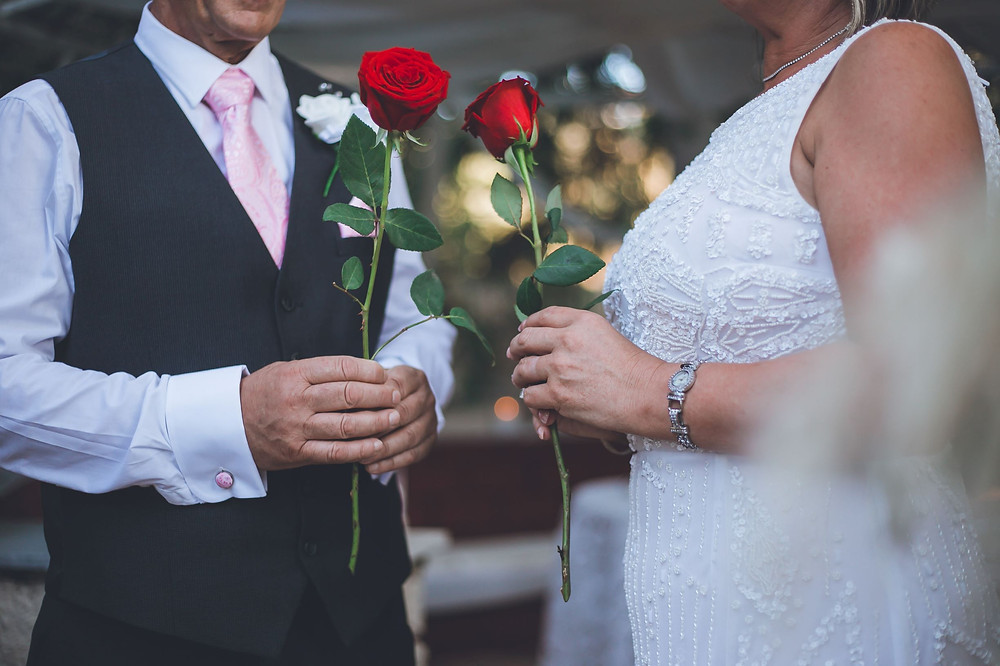 A close-up of the rose ceremony between a bride and groom at the altar with a single red rose in each one's hands.