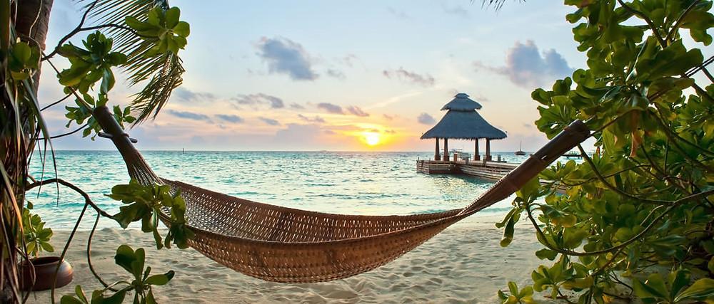 A Caribbean island sunset on the beach where a hammock awaits you