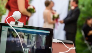A couple getting married beside a small wedding party as they live-stream the ceremony to friends and family, who are displayed with smiling faces on the laptop screen.