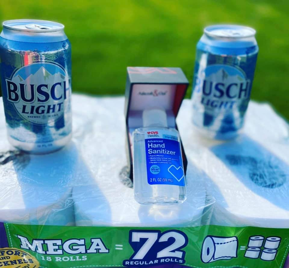 Hand sanitizer in a ring box sitting between two cans of Busch Light beer, all staged on top of a 72-pack of toilet paper rolls