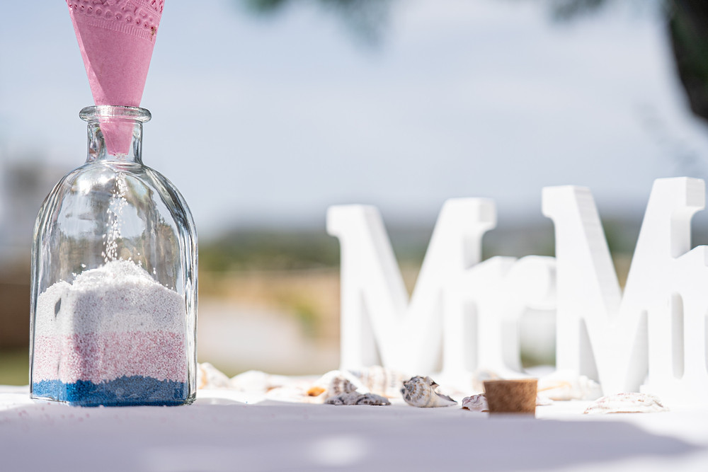A close-up of the bottle during a sand ceremony on a Greek island in the sun.