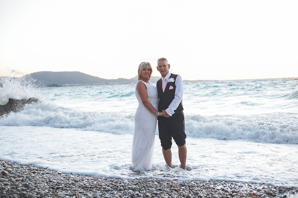 Newlyweds posing for a post-wedding ceremony photo at sunset as they stand with their feet in the Aegean sea on the shore, waves crashing on the rock in the water behind them.