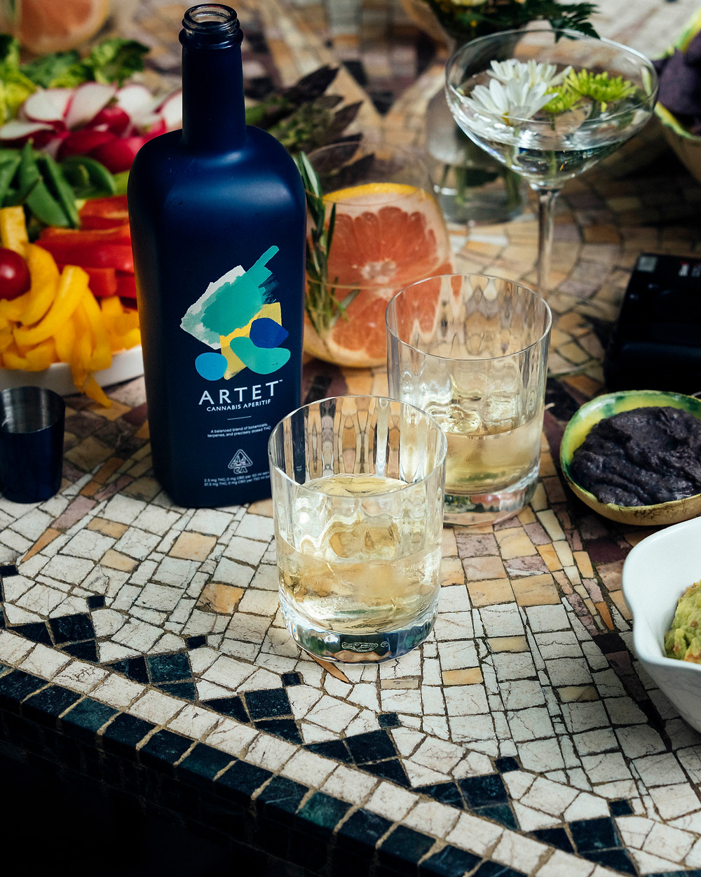 A bottle of Artet with half-filled glasses on a mosaic table topped with slices of various fruit