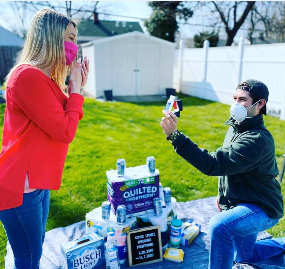 A groom proposes to his bride on one knee, both of them wearing masks, in front of a pile of toilet paper and Busch Light beers as he holds up a ring box containing a mini-bottle of hand sanitizer.