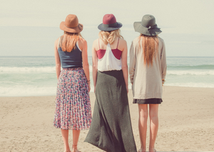 Three ladies dressed in summer attire, barefoot on the beach, facing the sea