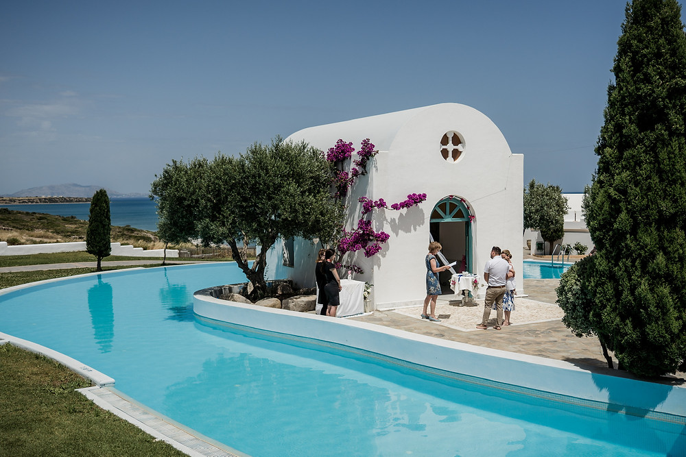 A couple getting married outside of a small while Greek orthodox chapel beside a pool that overlooks the Aegean sea.