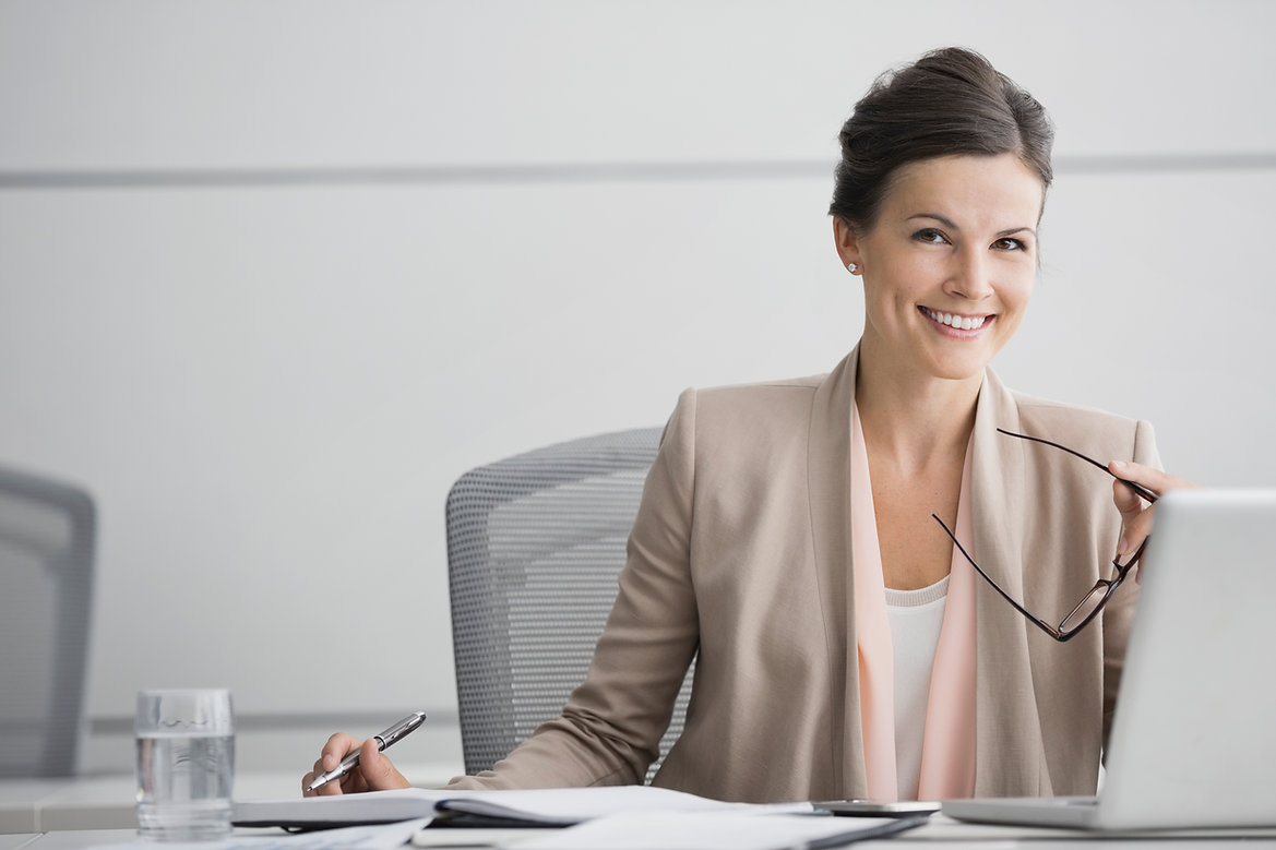 Image of a smiling woman sitting on a chair in an office