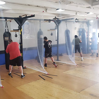 An adult male, young adult male and adult female member are in view. The members are at their stations hitting a heavy bag with plastic between them to give them the upmost safety.