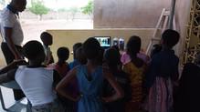 Children watching a movie with a speaker