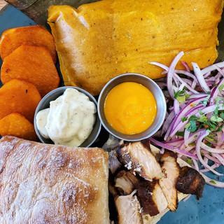 Lurín Brunch. Pan con chicharrón, chicken tamal, camote, ciabatta bread, salsa criolla, ají amarillo, homemade mayo.