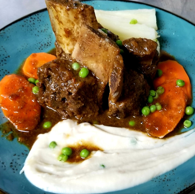 Seco de Carne. Certified Angus short ribs, slow cooked in chicha de jora and cilantro. Boiled yuca, green peas, carrots, pallar puree, white rice.