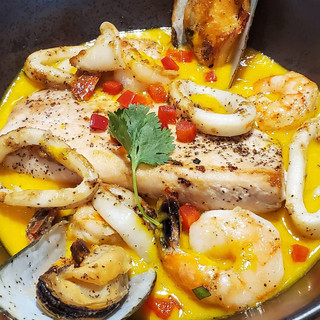 Pescado a lo Macho. Pan seared fish. Calamar, mussels and shrimp. Creamy ají amarillo and white wine sauce. Fried yuca, white rice.