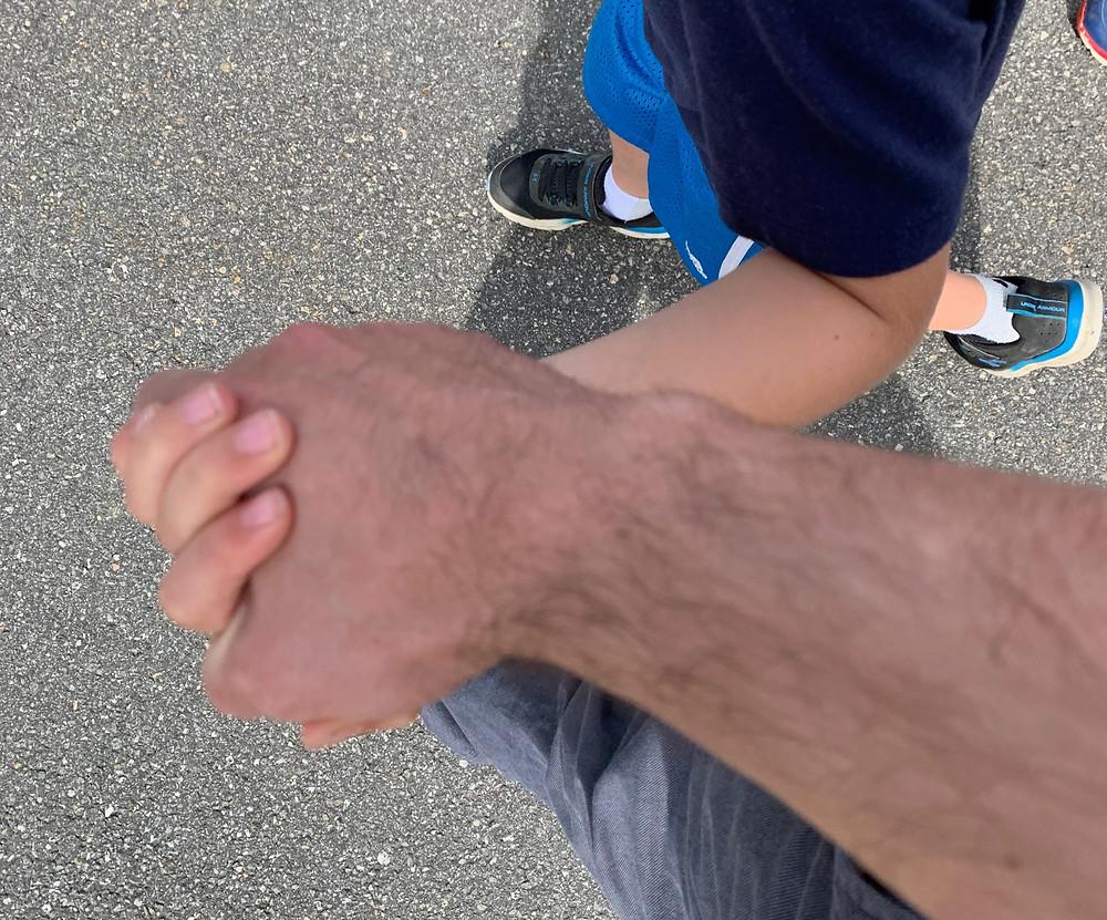 Matt holds hands with a student