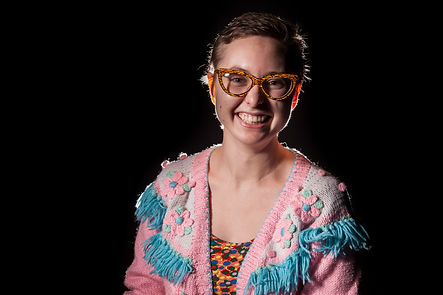 Bethany smiles into the camera with her short brown hair and smiling eyes and face.  She wears glasses and a multi textured pink sweater.