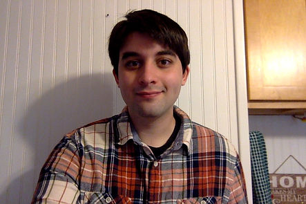 Noah sits in front of a paneled white wall smiling into the camera.  He has short brown hair and is wearing a plaid shirt.