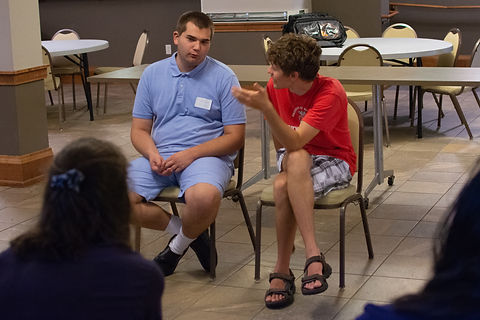 Image of 2 students talking to each other sitting in chairs