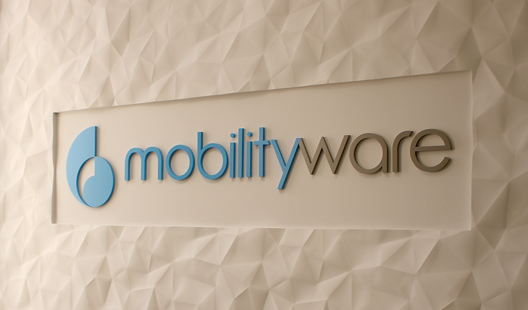 White, geometric, textured wall, with horizontal, smooth inset with dimensional Mobilityware logo