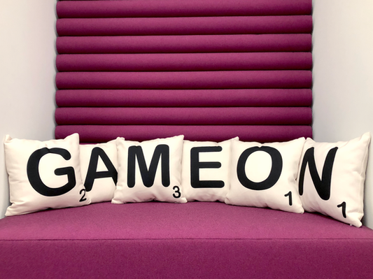 Six square pillows designed to look like Scrabble pieces spelling out GAME ON, sitting on a plum colored bench