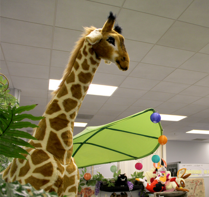 Photo of a stuffed giraffe next to some green leaves in an office setting