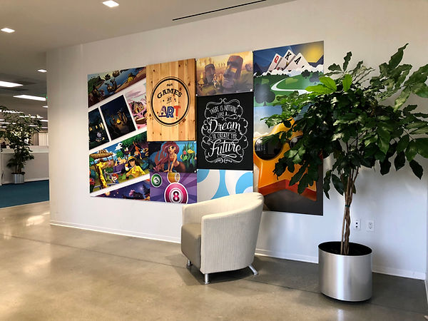 "A white wall in an office space with a collage of images and quotes ""Our Games are Art"" and ""There is nothing like a dream to create the future - Victor Hugo"". In front of the wall, a white chair and a potted plant."