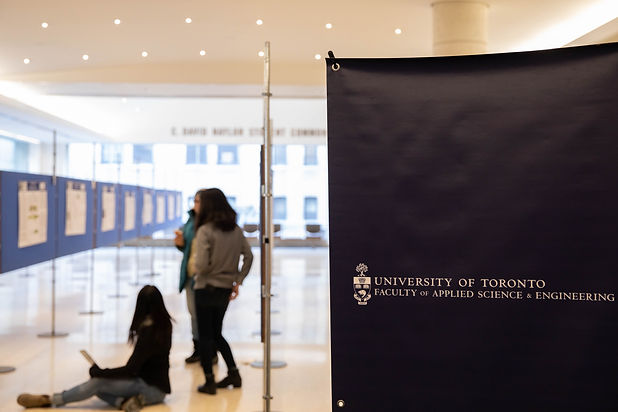Small group of students look around an empty Discovery symposium, the UofT FASE banner is in view