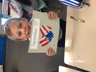 PES Student holding up his 9/11 Art Project that helped him remember the USA history.