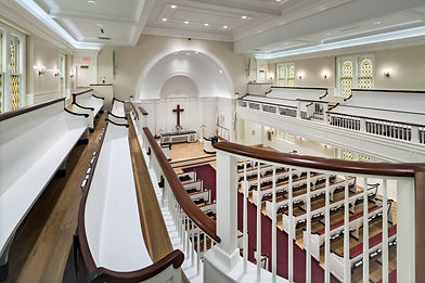 looking down at pew benches from the upper seating area