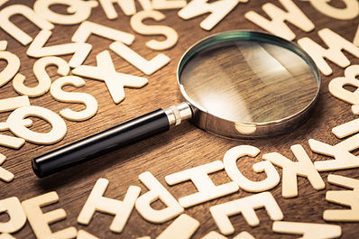 Magnifying glass with many wood letters of English alphabets, searching words to communica