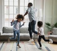 father-and-two-children-dancing-in-livin
