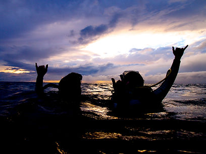 Divers above water at sunset